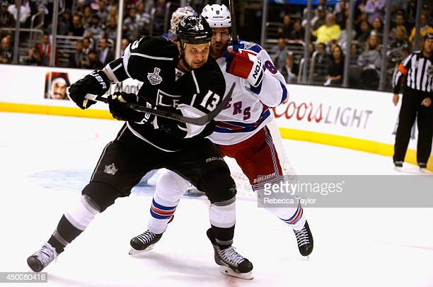 Kevin Klein of the New York Rangers pressures Kyle Clifford of the Los Angeles Kings during the third period of Game One of the 2014 Stanley Cup...
