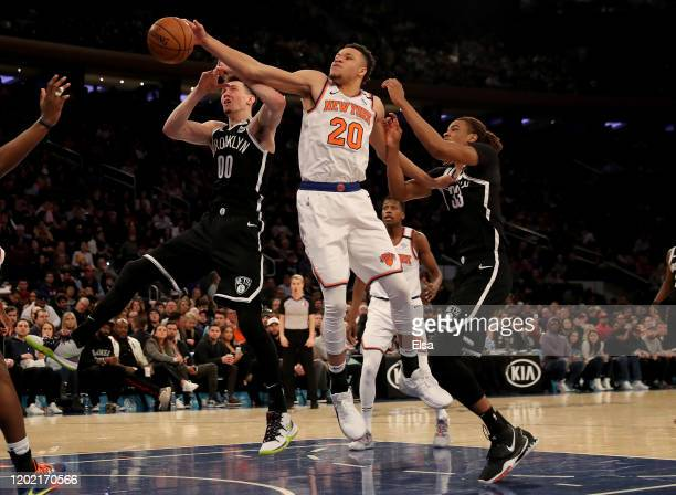 Kevin Knox II of the New York Knicks knocks away the ball as Rodions Kurucs and Nicolas Claxton of the Brooklyn Nets defend in the second half at...
