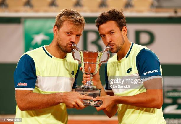 Kevin Krawietz and Andreas Mies of Germany kiss the winners trophy following victory in their Men's Doubles Final on Court Philippe-Chatrier against...