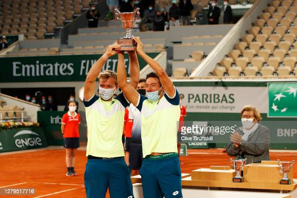 Kevin Krawietz and Andreas Mies of Germany lift the winners trophy following victory in their Men's Doubles Final on Court Philippe-Chatrier against...