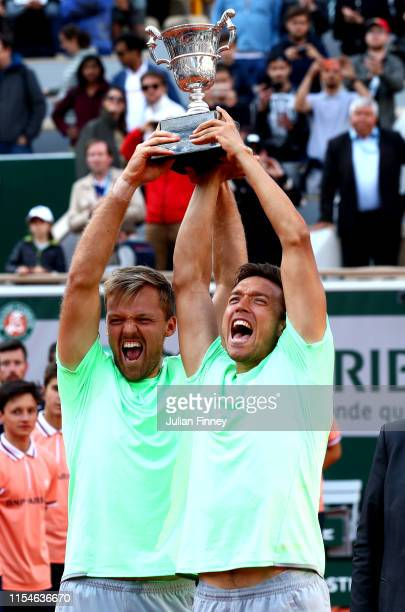 Kevin Krawietz of Germany and partner Andreas Mies of Germany lift the trophy as they celebrate victory during the mens doubles final against Jeremy...