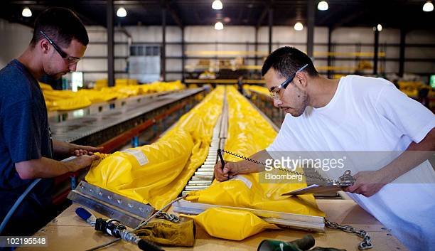 Kevin Krivoy left and Ivan Lopez right work on oil booms for Prestige Products in Walker Michigan US on Thursday June 17 2010 Michigan's depressed...