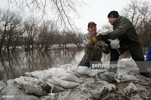 Kevin Kroke and John Simonson help build a sandbag levee along River Drive March 24 2009 in Fargo North Dakota Most of the schools in the area are...