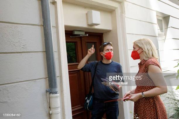 Kevin Kuehnert , deputy SPD head, and parliament candidate Wiebke Neumann , wait at the entrance of a residential building to speak to a local in the...