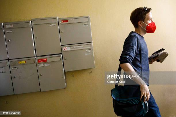 Kevin Kuehnert, deputy SPD leader, walks past mailboxes in a residential building during the launch of the SPD's door-to-door campaigning ahead of...