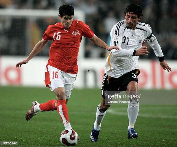 Kevin Kuranyi of Germany tackles Tranquillo Barnetta of Switzerland runs with the ball during the friendly match between Germany and Switzerland at...