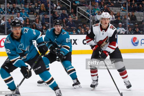 Kevin Labanc and Mikkel Boedker of the San Jose Sharks along with Christian Dvorak of the Arizona Coyotes look during a NHL game at SAP Center at San...