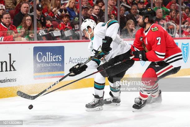 Kevin Labanc of the San Jose Sharks and Brent Seabrook of the Chicago Blackhawks chase the puck in the first period at the United Center on December...