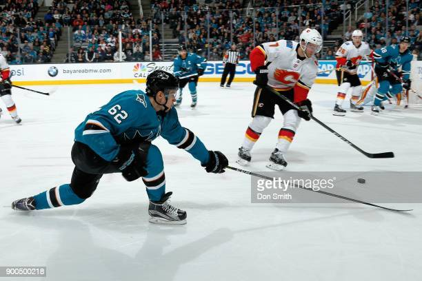 Kevin Labanc of the San Jose Sharks reaches to get the puck away from TJ Brodie of the Calgary Flames at SAP Center on December 28 2017 in San Jose...