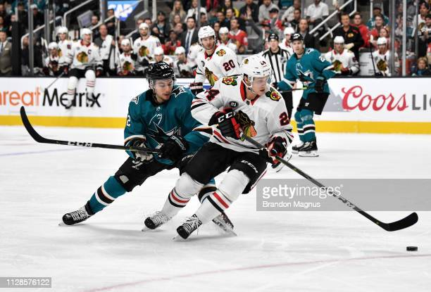 Kevin Labanc of the San Jose Sharks skates after the puck against Dominik Kahun of the Chicago Blackhawks at SAP Center on March 3 2019 in San Jose...