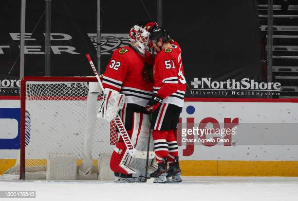 Kevin Lankinen of the Chicago Blackhawks celebrates with Ian Mitchell of the Chicago Blackhawks after their team defeated the Carolina Hurricanes 6-4...