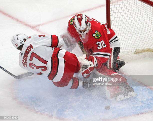 Kevin Lankinen of the Chicago Blackhawks makes a save against Andrei Svechnikov of the Carolina Hurricanes as Svechnikov slips and crashes into him...