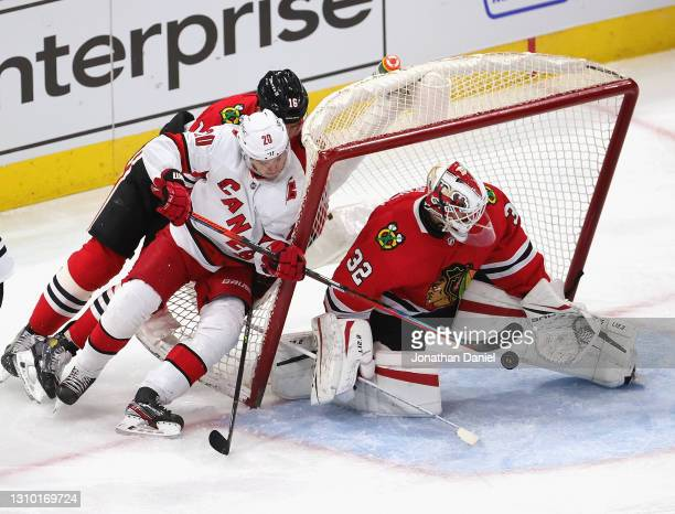 Kevin Lankinen of the Chicago Blackhawks makes a save as Sebastian Aho of the Carolina Hurricanes and Nikita Zadorov knock over the net at the United...