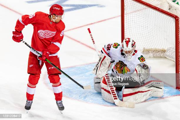 Kevin Lankinen of the Chicago Blackhawks takes the shot off his helmet as Mathias Brome of the Detroit Red Wings tries to tip it during an NHL game...