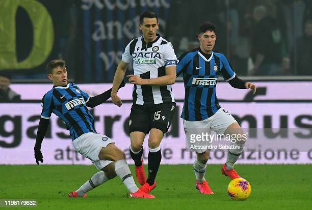 Kevin Lasagna of Udinese Calcio competes for the ball with Nicolò Barella of FC Internazionale and Alessandro Bastoni of FC Internazionale during the...