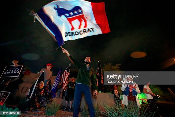 Kevin, last name withheld, waves a Democrat flag in opposition of a Republican-led protest on the Nevada vote by Donald Trump supporters outside...