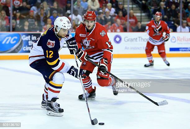 Kevin Lebanc of the Barrie Colts skates with the puck as Graham Knott of the Niagara IceDogs defends during the second period in Game Four of the...