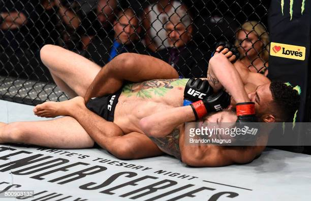 Kevin Lee attempts to secure a rear choke submission against Michael Chiesa in their lightweight bout during the UFC Fight Night event at the...