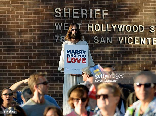 Kevin Lee Light known as West Hollywood Jesus holds a sign as he celebrates the US Supreme Court ruling during a community rally on June 26 2013 in...