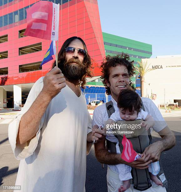 Kevin Lee Light known as West Hollywood Jesus poses with Perez Hilton and his son Perez Jr as they celebrate the US Supreme Court ruling during a...