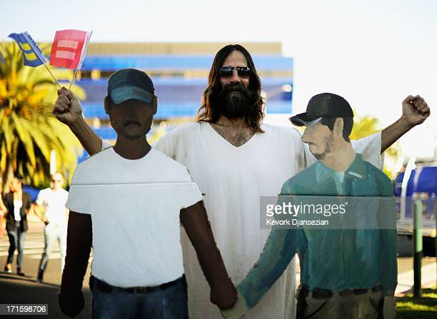 Kevin Lee Light known as West Hollywood Jesus stands in between cardboard cutouts of two men hoding hands as he celebrates the US Supreme Court...
