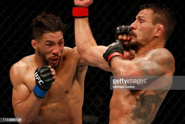 Kevin Lee punches Rafael Dos Anjos of Brazil in their welterweight bout during the UFC Fight Night event at Blue Cross Arena on May 18, 2019 in...