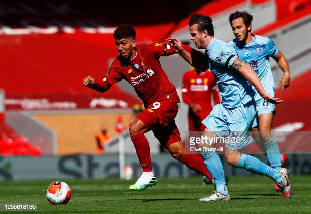 Kevin Long of Burnley puts pressure on Roberto Firmino of Liverpool during the Premier League match between Liverpool FC and Burnley FC at Anfield on...