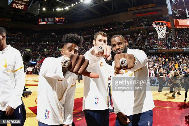 Kevin Love Iman Shumpert and LeBron James of the Cleveland Cavaliers show off their rings during the NBA Championship ring ceremony prior to the game...