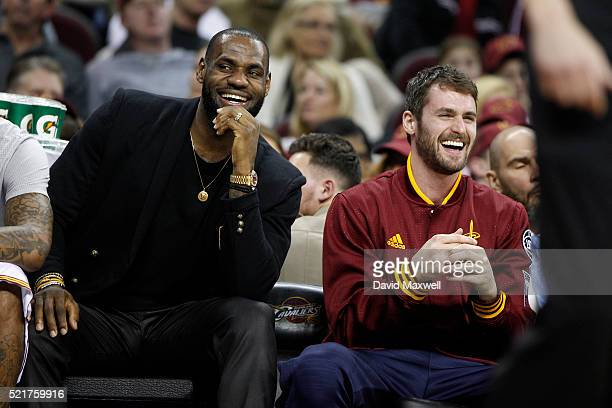 Kevin Love of the Cleveland Cavaliers and LeBron James watch from the bench during the game against the Detroit Pistons at Quicken Loans Arena on...