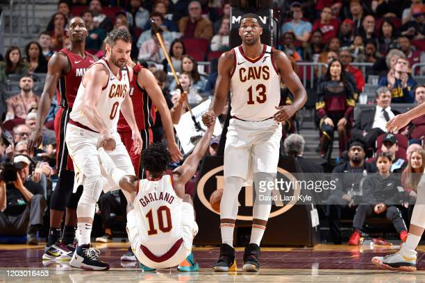 Kevin Love of the Cleveland Cavaliers and Tristan Thompson of the Cleveland Cavaliers helps up Darius Garland of the Cleveland Cavaliers on February...