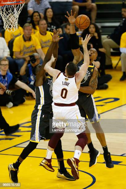 Kevin Love of the Cleveland Cavaliers attempts a shot defended by Draymond Green and David West of the Golden State Warriors in Game 2 of the 2018...