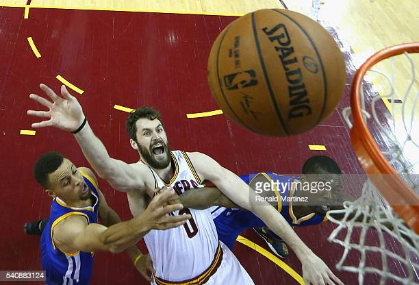 Kevin Love of the Cleveland Cavaliers shoots the ball against Stephen Curry of the Golden State Warriors and Harrison Barnes during the second half...