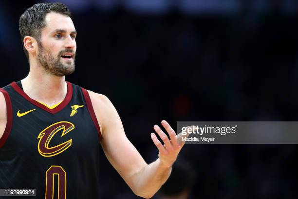 Kevin Love of the Cleveland Cavaliers talks to a member of the coaching staff on the bench during the first half of the game against the Boston...