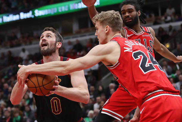 Kevin Love of the Cleveland Cavaliers tries to get off a shot under pressure from Lauri Markkanen of the Chicago Bulls at the United Center on March...