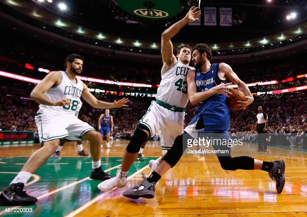 Kevin Love of the Minnesota Timberwolves attempts to drive the baseline in front of Kris Humphries and Vitor Faverani of the Boston Celtics in the...
