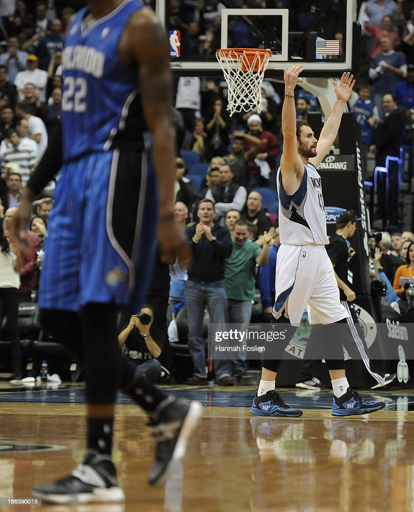 Kevin Love #42 of the Minnesota Timberwolves celebrates making a three point shot in the final seconds of the fourth quarter to tie the game as Solomon Jones #22 of the Orlando Magic walks back to his bench during the season opening game on October 30, 2013 at Target Center in Minneapolis, Minnesota. The Timberwolves defeated the Magic 120-115 in overtime.