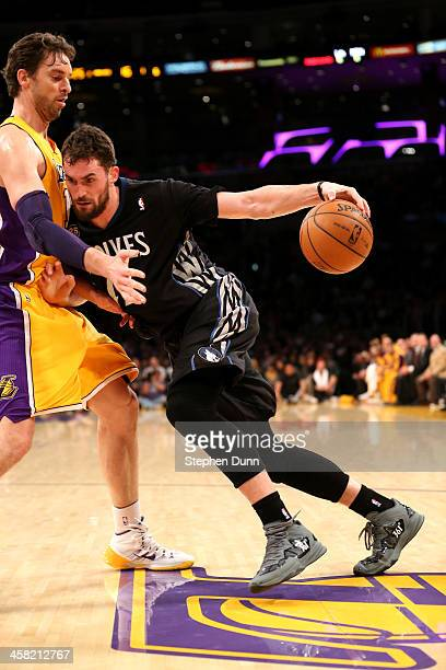 Kevin Love of the Minnesota Timberwolves drives against Pau Gasol of the Los Angeles Lakers at Staples Center on December 20, 2013 in Los Angeles,...