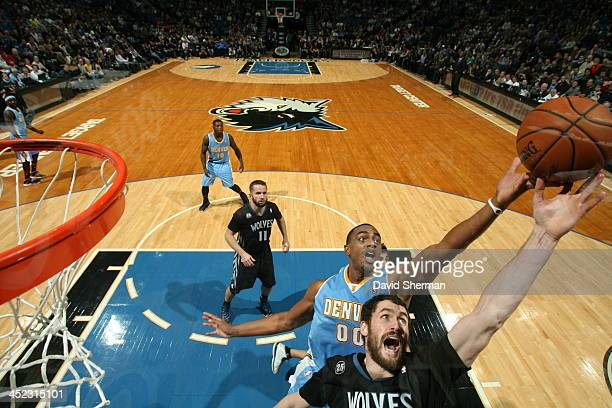 Kevin Love of the Minnesota Timberwolves reaches for a rebound against Darrell Arthur of the Denver Nuggets on November 27 2013 at Target Center in...