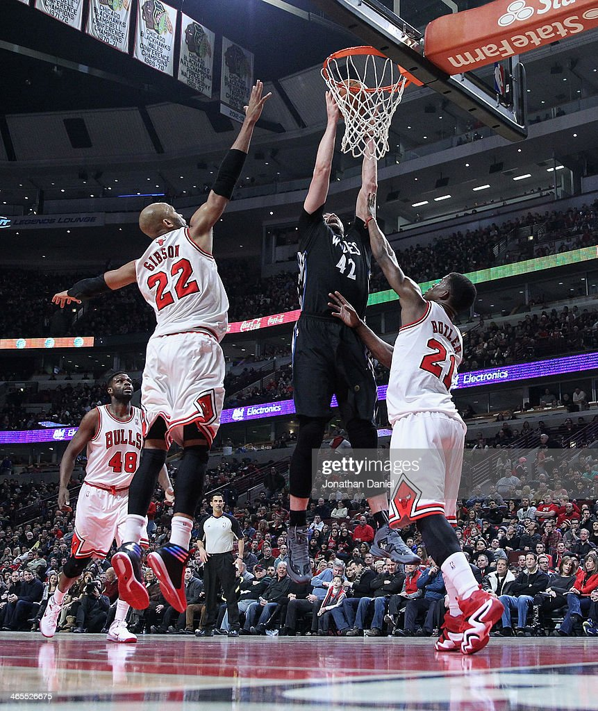 Kevin Love #42 of the Minnesota Timberwolves rebounds over Taj Gibson #22 and Jimmy Butler #21 of the Chicago Bulls at the United Center on January 27, 2014 in Chicago, Illinois. The Timberwolves defeated the Bulls 95-86.