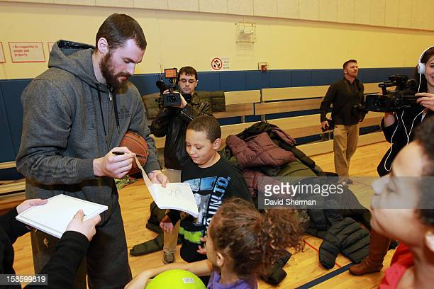 Kevin Love of the Minnesota Timberwolves signs autographs for kids participating in the Salvation Army's After School Program after delivering coats...