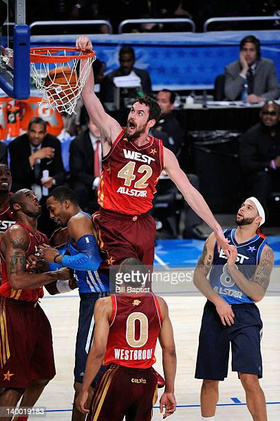 Kevin Love of the Western Conference AllStars dunks against Dwight Howard and Deron Williams of the Eastern Conference AllStars during the 2012 NBA...