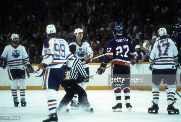 Kevin Lowe of the Edmonton Oilers argues with John Tonelli of the New York Islanders during the 1984 Stanley Cup Finals in May 1984 at the Northlands...
