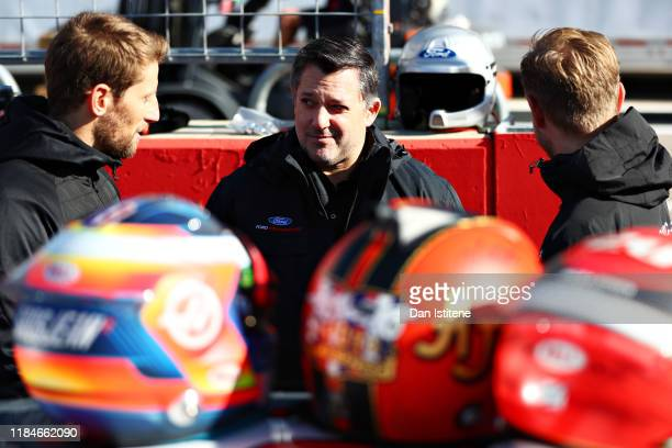 Kevin Magnussen of Denmark and Haas F1 and Romain Grosjean of France and Haas F1 talk with Tony Stewart before driving the No.14 Haas Automation Ford...