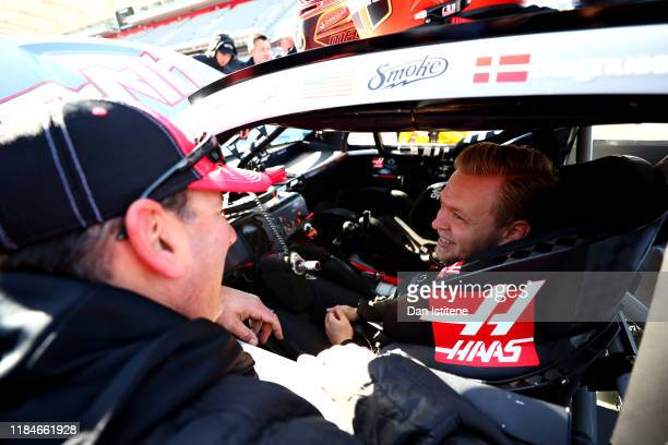 Kevin Magnussen of Denmark and Haas F1 talks with Tony Stewart before driving the No.14 Haas Automation Ford Mustang in a demonstration run during...
