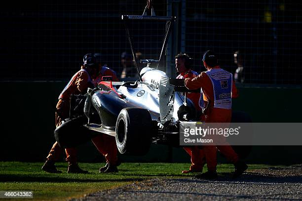 Kevin Magnussen of Denmark and McLaren Honda's car is lifted off the track after he crashed during practice for the Australian Formula One Grand Prix...