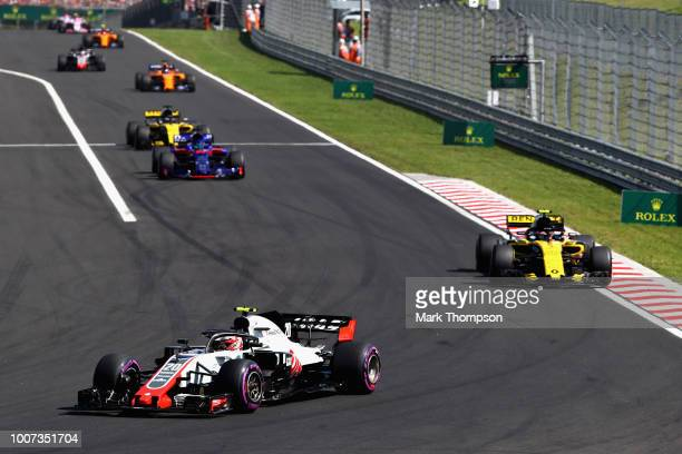 Kevin Magnussen of Denmark driving the Haas F1 Team VF18 Ferrari leads Carlos Sainz of Spain driving the Renault Sport Formula One Team RS18 on track...