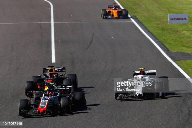 Kevin Magnussen of Denmark driving the Haas F1 Team VF18 Ferrari leads Daniel Ricciardo of Australia driving the Aston Martin Red Bull Racing RB14...
