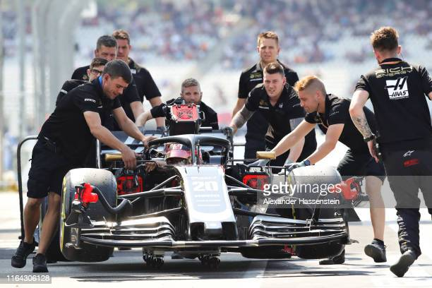 Kevin Magnussen of Denmark driving the Haas F1 Team VF-19 Ferrari is pushed down the pitlane after stopping on track during practice for the F1 Grand...