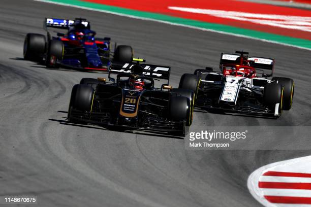 Kevin Magnussen of Denmark driving the Haas F1 Team VF-19 Ferrari leads Kimi Raikkonen of Finland driving the Alfa Romeo Racing C38 Ferrari and...