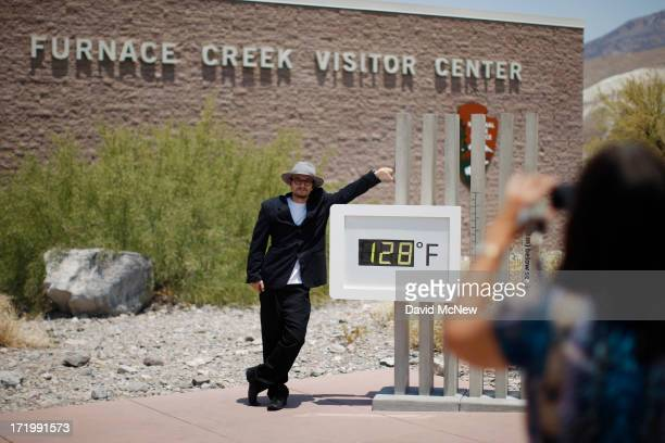 Kevin Martin of Corona, California poses for a snapshot by an unofficial thermometer reading at Furnace Creek Visitor Center reading 128 degrees as a...